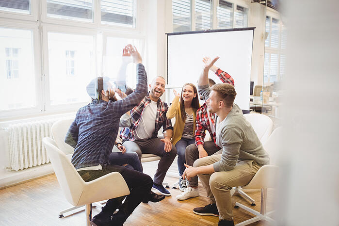 Excited creative business people giving high-five in meeting room at creative office-1