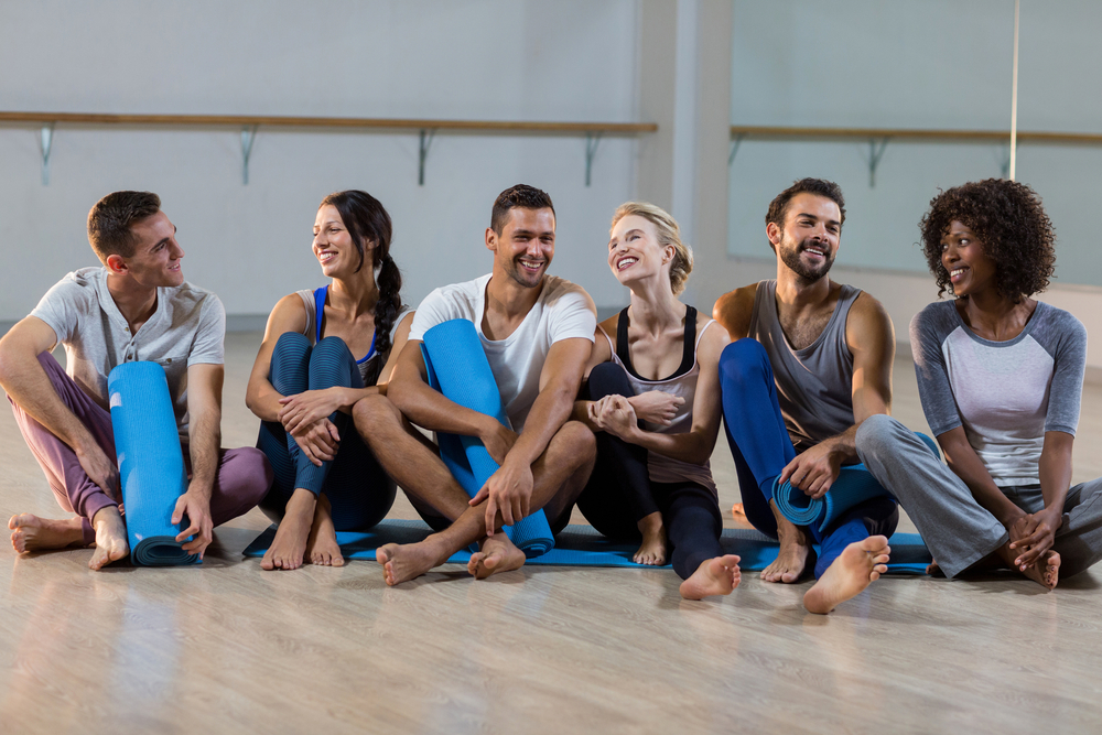 Group of people sitting on floor in fitness studio