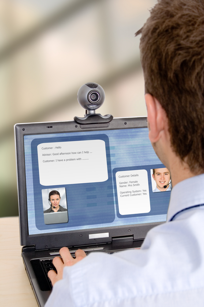 online customer support - business man having an online chat with another person via webcam and headsets