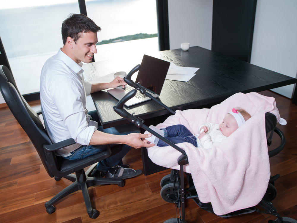 young man parent working on laptop computer at home office and take care of baby-1