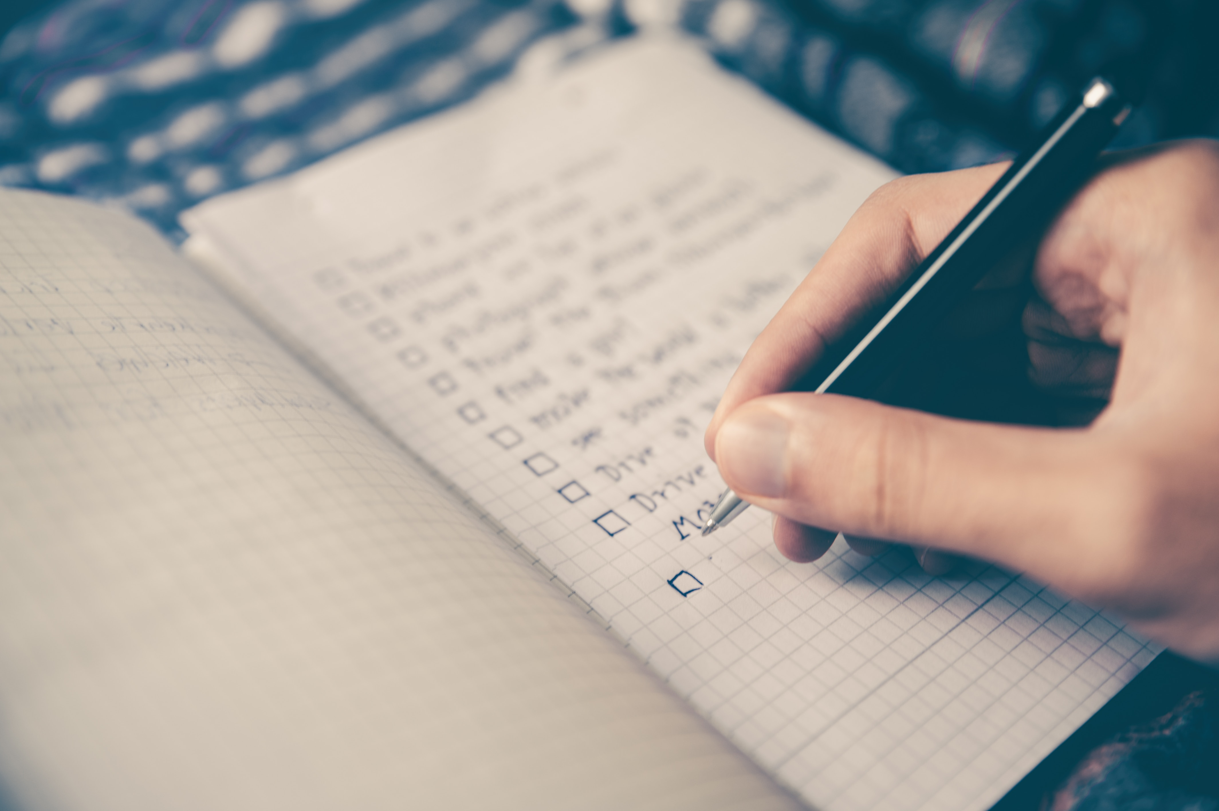 hand writing in a grid-style notebook, checking off items in a to do list for new years resolutions